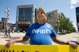 Bob Kunst of Miami Beach, Fla. wears a Hillary Rodham Clinton mask and holds an anti-Hillary poster outside the Quicken Loans Arena in Cleveland, Aug. 5, 2015.