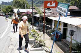 Women walk near a sign on their way home marking a tsunami evacuation route a day after a 7.8 magnitude earthquake struck far out at sea near Padang, West Sumatra province, Indonesia, March 3, 2016.