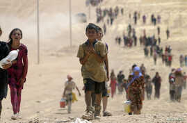 Children from the minority Yazidi sect, fleeing violence from Islamic State militants Sinjar, Iraq, make their way toward the town of Elierbeh of Al-Hasakah Governorate, near the Syrian border, Aug. 10, 2014.
