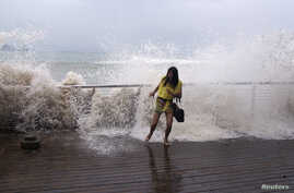 A woman reacts as a storm surge jumps a barrier on the shore as Typhoon Usagi approaches Shenzhen, Guangdong province, September 22, 2013.