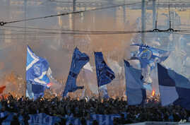 FILE - In this April 28, 2012, photo, Zenit's fans march prior to the match of their team in the national soccer championship in St. Petersburg, Russia. A new report seen by the Associated Press shows Russia has made progress fighting football racism