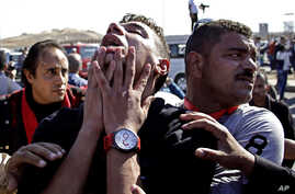 An anti-Hosni Mubarak protester reacts after hearing the verdict of the trial of the former Egyptian President outside a police academy on the outskirts of Cairo Saturday, Nov. 29, 2014.