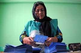 Independent Election Commission (IEC) employee counts the ballot at a polling station in Mazar-i-Sharif, Afghanistan, June 14, 2014.