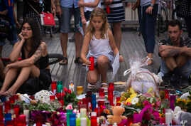 A girl places a candle after a terror attack that killed 14 people and wounded over 120 in Barcelona, Spain, Aug. 20, 2017. (