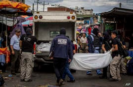 Police investigators carry a body to a forensic vehicle after a shootout between private security guards and gang members at the central market in San Salvador, El Salvador, March 15, 2017.  At least 30 people, mostly gang members, died in the last 2