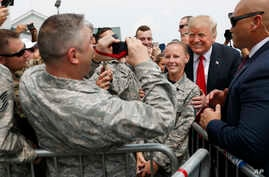 President Donald Trump poses for photographs while greeting members of the military on the tarmac upon his arrival on Air Force One at Francis S. Gabreski Airport in Westhampton, New York,  Aug. 17, 2018.