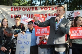 "The founder of ""Let America Vote"" speaks to protesters gathered outside Saint Anselm College in Manchester, N.H., where the Trump administration's commission on voter fraud met on Sept. 12, 2017."