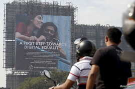 FILE - Motorists ride past a billboard displaying Facebook's Free Basics initiative in Mumbai, India.