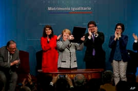 Chile's President Michelle Bachelet holds up a portfolio containing her signed proposal for a same-sex marriage bill at La Moneda presidential palace in Santiago, Chile, Aug. 28, 2017.