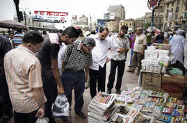 Egyptians look at newspapers displayed at a kiosk outside the Al-Fatah Mosque in Cairo, May 25, 2012.