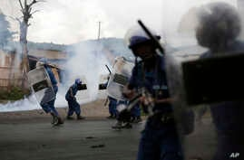 Burundi riot police using tear gas give chase to demonstrators during clashes in Bujumbura, April 29, 2015.