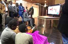 People follow Zimbabwe Electoral Commission announcement of the July 30, polls at a hotel in Harare, Zimbabwe, Aug. 2, 2018.