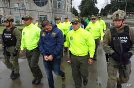 This undated photo released by Colombia's National Police shows officers escorting a man whom police identified as Ecuadorean drug trafficker Edison Prado after his April 2017 arrest on an indictment by a Florida federal court. A few months after his