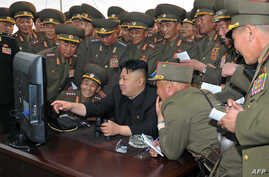 FILE - North Korean leader Kim Jong Un, center, looks at a computer as he inspects a shelling drill of a long-range artillery sub-unit tasked to hit major targets in the southwestern waters at undisclosed place in North Korea.