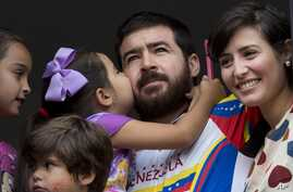 Maria Daniela kisses her father Daniel Ceballos, former mayor of the western city of San Cristobal, as he looks out from an apartment window with his wife Patricia de Ceballos, right, daughter Maria Veronica, left, and son Juan Daniel in Caracas, Ven