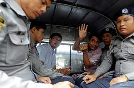 Detained Reuters journalists Wa Lone and Kyaw Soe Oo sit beside police officers as they leave court in Yangon, Myanmar, July 9, 2018. The two were charged with breaching the colonial-era Official Secrets Act.