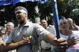 Ukrainian opposition supporters sing national anthem during a protest, Kiev, July 30, 2012.