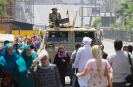 An army soldier stands alert over an armored vehicle near Nahda Square, where supporters of Egypt's ousted President Mohammed Morsi have installed their camp near Cairo University in Giza, southwestern Cairo, Egypt, Aug. 12, 2013.
