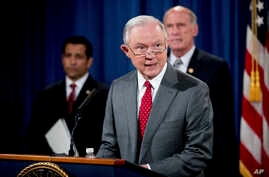 Attorney General Jeff Sessions, accompanied by, from left, National Counterintelligence and Security Center Director William Evanina, Director of National Intelligence Dan Coats, speaks during a briefing at the Justice Department in Washington, Aug.