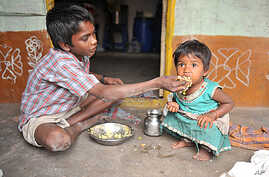 """An Indian boy feeds his sister at their home in a slum in Hyderabad.  Levels of under-nutrition in the country were """"unacceptably high"""" despite impressive GDP growth, Prime Minister Manmohan Singh said Tuesday and added that the problem of malnutriti"""