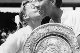 Althea Gibson holds the Wimbledon womens singles trophy as she gets a kiss from Darlene Hard, after Gibson defeated Hard in the final match at Wimbledon, England, in this July 6, 1957 file photo.  (AP Photo)