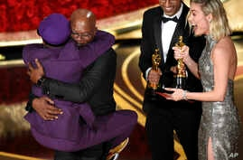 """Samuel L. Jackson, center left, embraces Spike Lee, winner of the award for best adapted screenplay for """"BlacKkKlansman"""" as Brie Larson, right, looks on, at the Oscars on Feb. 24, 2019, at the Dolby Theatre in Los Angeles."""