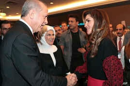 Turkey's President Recep Tayyip Erdogan, left, accompanied by his wife Emine, center, shakes hands with Jordan's Queen Rania, at a conference in Istanbul, Oct. 4, 2018.