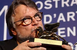 """Guillermo del Toro kisses the Golden Lion for best film for """"The Shape Of Water"""" during the awards photo call at the 74th Venice Film Festival at the Venice Lido, Italy, Sept. 9, 2017."""