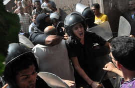 Egyptians security forces escort a protester out of the al-Fatah mosque and through angry crowds following a day of fierce street battles that left scores of people dead, near Ramses Square in downtown Cairo, Egypt, Aug. 17, 2013.
