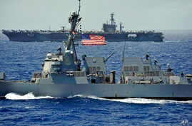 FILE - The USS Chung-Hoon guided-missile destroyer, front, and the USS Nimitz aircraft carrier are underway during the Great Green Fleet demonstration portion of the Rim of the Pacific (RIMPAC) 2012 exercise, July 18, 2012.