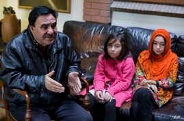 In this Nov. 29, 2018 photo, Mir Aman speaks to The Associated Press with his daughters Shahnaz, right, and Shakeela, in Islamabad, Pakistan.