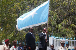 Somalia's newly elected President Mohamed Abdullahi Mohamed, right, flanked by outgoing president Hassan Sheikh Mohamud carries their national flag during the hand-over ceremony at the Presidential palace in Somalia's capital Mogadishu, Feb. 16, 2017