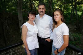 In this Aug. 9, 2017 photo family members of 18-year-old murder victim Andrew Oneschuk, stand for a portrait at their home in Wakefield, Mass. Devon Arthurs, co-founder of the neo-Nazi group Atomwaffen, was arrested on murder charges in the shooting