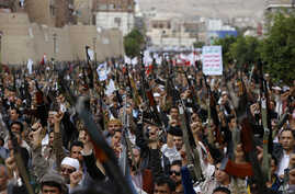 Shiite rebels known as Houthis hold up their weapons as they chant slogans during a rally against Saudi-led airstrikes in Sanaa, Yemen, Friday, July 24, 2015