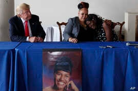 Republican presidential candidate Donald Trump, left, looks on as Shalga Hightower, center, hugs family spokesman Charmil Davis during a meeting, Sept. 2, 2016, in Philadelphia. Hightower's daughter, Iofemi Hightower, was murdered in a 2007 attack at