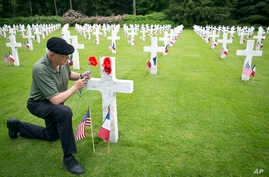 Mark Shively, from Beaverton, Oregon leaves flowers at the grave of his grandfather's unit commander, World War I U.S. Marine Corps Lt. Carleton Burr, during Memorial Day weekend at Aisne-Marne American Cemetery in Belleau, May 26, 2018.