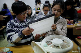FILE - Students hold a HEPA filter as they prepare to put it on a fan at a workshop to learn how to make a DIY air purifier at a college in Beijing.
