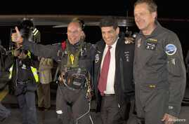 The Solar Impulse plane's project president and pilot, Bertrand Piccard (L) celebrates with co-founder and CEO Andre Borschberg (R) and Moroccan Agency for Solar Energy (MASEN) CEO Mustapha Bakkoury after the plane landed following a 19-hour flight f