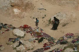 A woman and her children, who left the besieged Islamic State-held village of Baghuz, Syria, scramble over a rocky hillside to be checked by U.S-backed Syrian Democratic Forces, March 14, 2019.