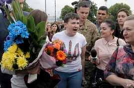 Ukrainian pilot Nadezhda Savchenko, center, speaks to the media upon her arrival at Boryspil airport outside Kiev, Ukraine, May 25, 2016.