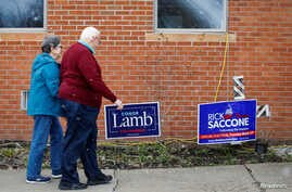 A couple arrive at a polling place in Carnegie, Pennsylvania, March 13, 2018.