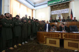 Forty-nine defendants left, attend their trial at the Primary Court in Kabul, Afghanistan, on charges related to the mob killing of an Afghan woman, May 2, 2015.