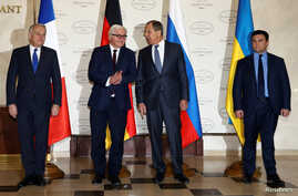 From right, Foreign Ministers Pavlo Klimkin of Ukraine, Sergei Lavrov of Russia, Frank-Walter Steinmeier of Germany and Jean-Marc Ayrault of France pose for a picture as they gather for talks on the crisis in eastern Ukraine, in Minsk, Belarus, Nov.