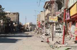 The main street in the Dawasa neighborhood of western Mosul was a hub for restaurants and nightlife more than a decade ago.  Now the shops are burnt out or destroyed and the area is abandoned on March 10, 2017. (H.Murdock/VOA)