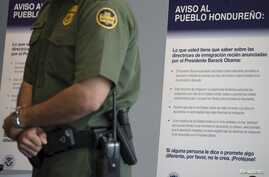A Customs and Border Protections officer stands in front of a Spanish-language poster being used in a campaign to discourage illegal border crossings into the United States during a news conference at the Ysidro border crossing in San Ysidro, Califor