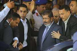 Egypt's President-elect Mohammed Morsi is guarded by presidential security as he leaves Friday prayers at Al-Azhar mosque, in Cairo, Egypt, Friday, June 29, 2012.