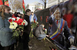 People bring flowers to the Venezuelan embassy to pay tribute to the late Venezuelan President Hugo Chavez, in Minsk Mar. 6, 2013.