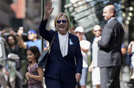 US Democratic presidential nominee Hillary Clinton waves to the press as she leaves her daughter's apartment building after resting on September 11, 2016, in New York.