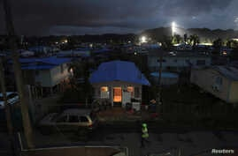 A house is lit up with the help of a generator next to houses in the dark after Hurricane Maria damaged the electrical grid in September, in Dorado, Puerto Rico Jan. 15, 2018.