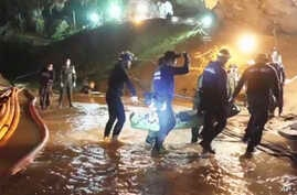 FILE - This undated from video released via the Thai NavySEAL Facebook Page on July 11, 2018, shows rescuers holding an evacuated boy inside the Tham Luang Nang Non cave in Mae Sai, Chiang Rai province, in northern Thailand.